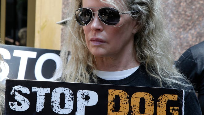 Animal rights activist and actress Kim Basinger holds a sign at protest against the dog-meat trade outside the South Korean consulate in Los Angeles, July 17, 2018.