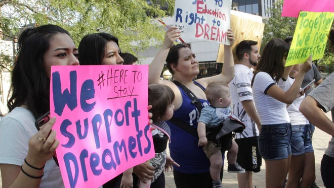 Protesters hold up signs in support of the Deferred Action for Childhood Arrivals program at a rally in Riehle Plaza in Lafayette on Aug. 15, 2017. President Donald Trump recently called to wind down the Obama-era program.