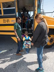 Head Start teachers, Whitney Henderson, top left, and Sharon Moton, far right, escort their students to a waiting bus for a ride home from school Friday afternoon. The Head Start program has a fleet of buses that is old and unreliable. Many of its buses are often out of service, making it difficult for the organization to get students to and from its programs.