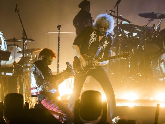 Adam Lambert kneels beneath Queen lead guitarist Brian