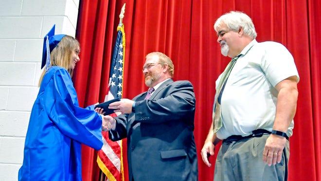 Jeffrey Layton (middle), Northwestern Local superintendent, and Mike Burkholder, former Northwestern High School principal, award Cortney Shelton her diploma in 2017.