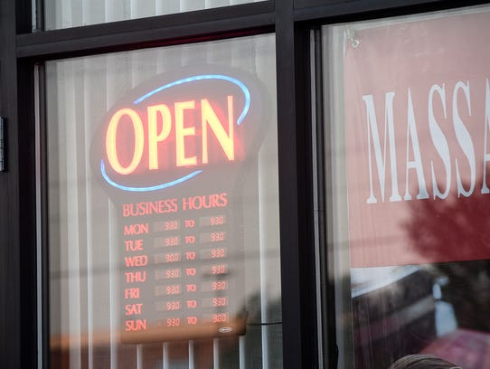 Signs hang in the window of a massage business Wednesday,