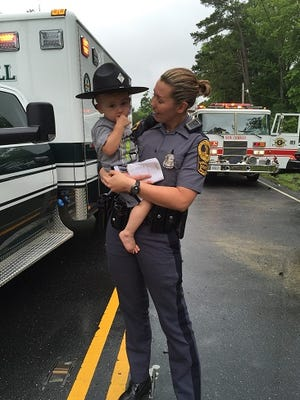 This June 16, 2016 submitted photo shows Virginia State Police trooper C. Smith comforting a small child involved in a two-vehicle crash in New Church about noontime. Several people were hospitalized, although their conditions were not immediately available.