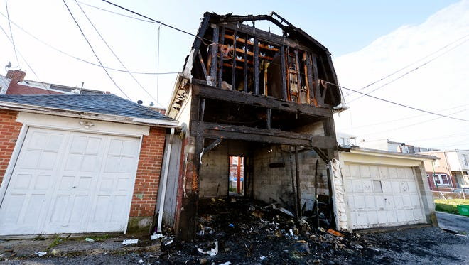A garage is shown several hours after a fire Wednesday. An early morning fire that spread to two garages in the 800 block of School Place, an alley parallel to and between West Princess Street and West Poplar Street, was ruled as arson, the York City Fire Department said.