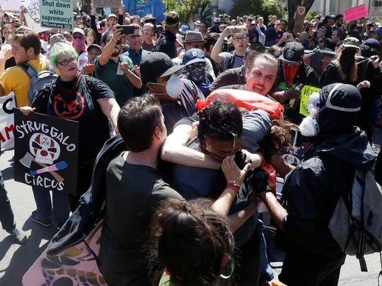 """Demonstrators clash during a free speech rally Sunday, Aug. 27, 2017, in Berkeley, Calif. Several thousand people converged in Berkeley Sunday for a """"Rally Against Hate"""" in response to a planned right-wing protest that raised concerns of violence and triggered a massive police presence. Several people were arrested for violating rules against covering their faces or carrying items banned by authorities. (AP Photo/Marcio Jose Sanchez)"""