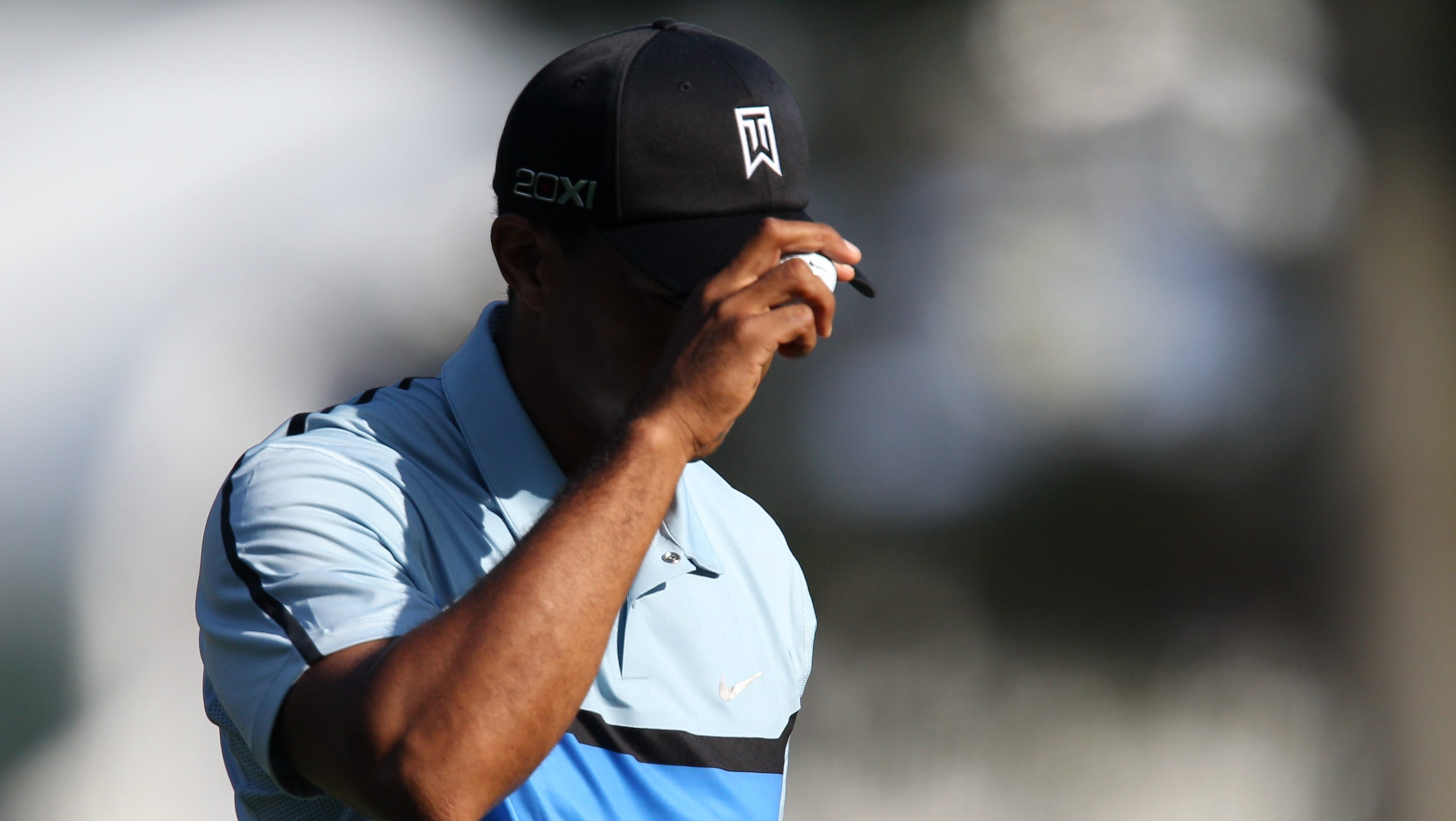 Tiger Woods tips his hat on 10 green.