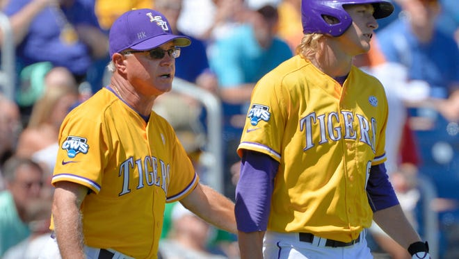 LSU coach Paul Mainieri wears a gold LSU Tigers jersey as he talks to LSU center fielder Andrew Stevenson in the third inning of an NCAA College World Series baseball elimination game against Cal State Fullerton at TD Ameritrade Park in Omaha, Neb., Tuesday, June 16, 2015. LSU was so disappointed in its performance in its College World Series opener Sunday that change was in order for Tuesday's game against Cal State Fullerton. The Tigers came out in gold jerseys and even coach Mainieri, who typically wears a wind shirt in the dugout put one on. (AP Photo/Ted Kirk)