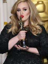 Adele plants a kiss on her Academy Award  in 2013.