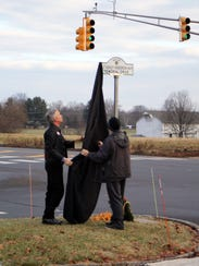 """Mark Henderson (right), father of Ashley Henderson-Huff, and Tom D'Alessio of Rolling Thunder, unveil the new street sign at the entrance to Montgomery Township High School, dubbing it """"1st Lt. Ashley Henderson-Huff Memorial Drive."""" Ashley was a Montgomery High School 2000 graduate and a military police officer killed during duty in Iraq in 2006."""