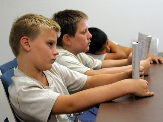 Bill Bruno, not pictured, reads to Thys Danzeisen, 8, left, Oliver Bourez, 10, and Adrian Gonzalez, 10, that are challenging their reading skills by following along and learning about heroes of history, Alan Shepard, during a week-long reading camp at Prosperity Avenue Baptist Church, Tulare.