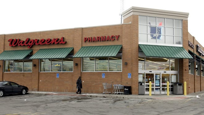 A customer walks to a Walgreens store in a Detroit.