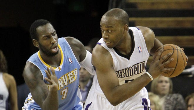 Sacramento Kings forward Carl Landry, right, protects the ball from Denver Nuggets forward J.J. Hicks during the first quarter of an NBA basketball game in Sacramento, Calif., Jan. 26, 2014.