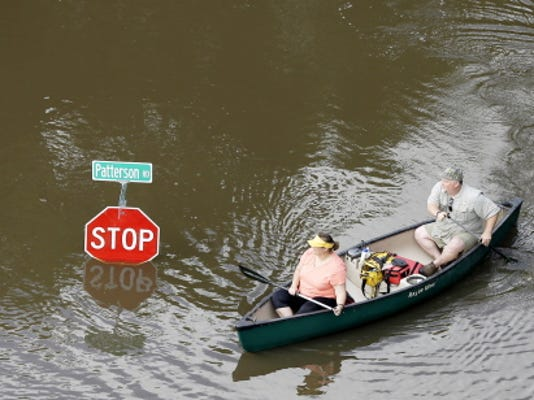 People canoe through floodwaters past a stop sign near Bear Creek Park on Saturday in Houston.