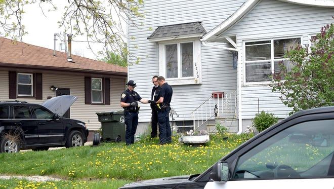 Fort Dodge Police officers Matt Weir, left, Larry Hedlund and Jacob Naatz investigate an accidental shooting, Wednesday, May 9, 2018, in Fort Dodge, Iowa. Richard Remme, of Fort Dodge, told police he was playing with his dog, Balew, on the couch and tossed the dog off his lap. He says when the pit bull-Labrador mix bounded back up, he must have disabled the safety on the gun in his belly band and stepped on the trigger causing the gun to fire and strike Remme in the leg.