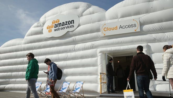 Visitors arrive at the cloud pavilion of Amazon Web Services at the 2016 CeBIT digital technology trade fair on March 14, 2016.
