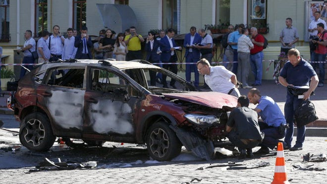 Forensic experts examine the wreckage of a burned car in Kiev, Ukraine, on July 20.