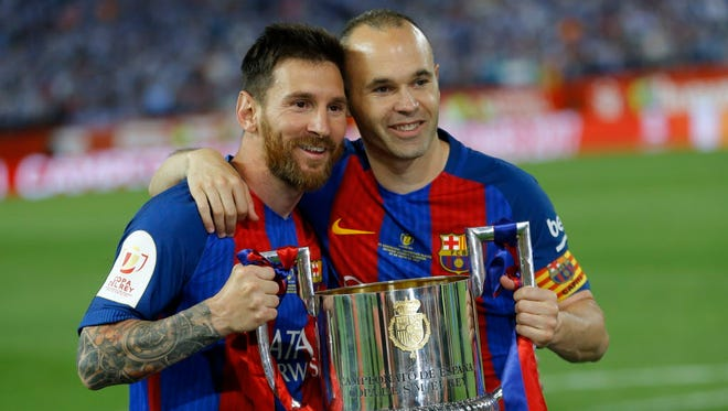 Barcelona's Lionel Messi and Andres Iniesta pose with the trophy after the Copa del Rey final soccer match between Barcelona and Alaves.