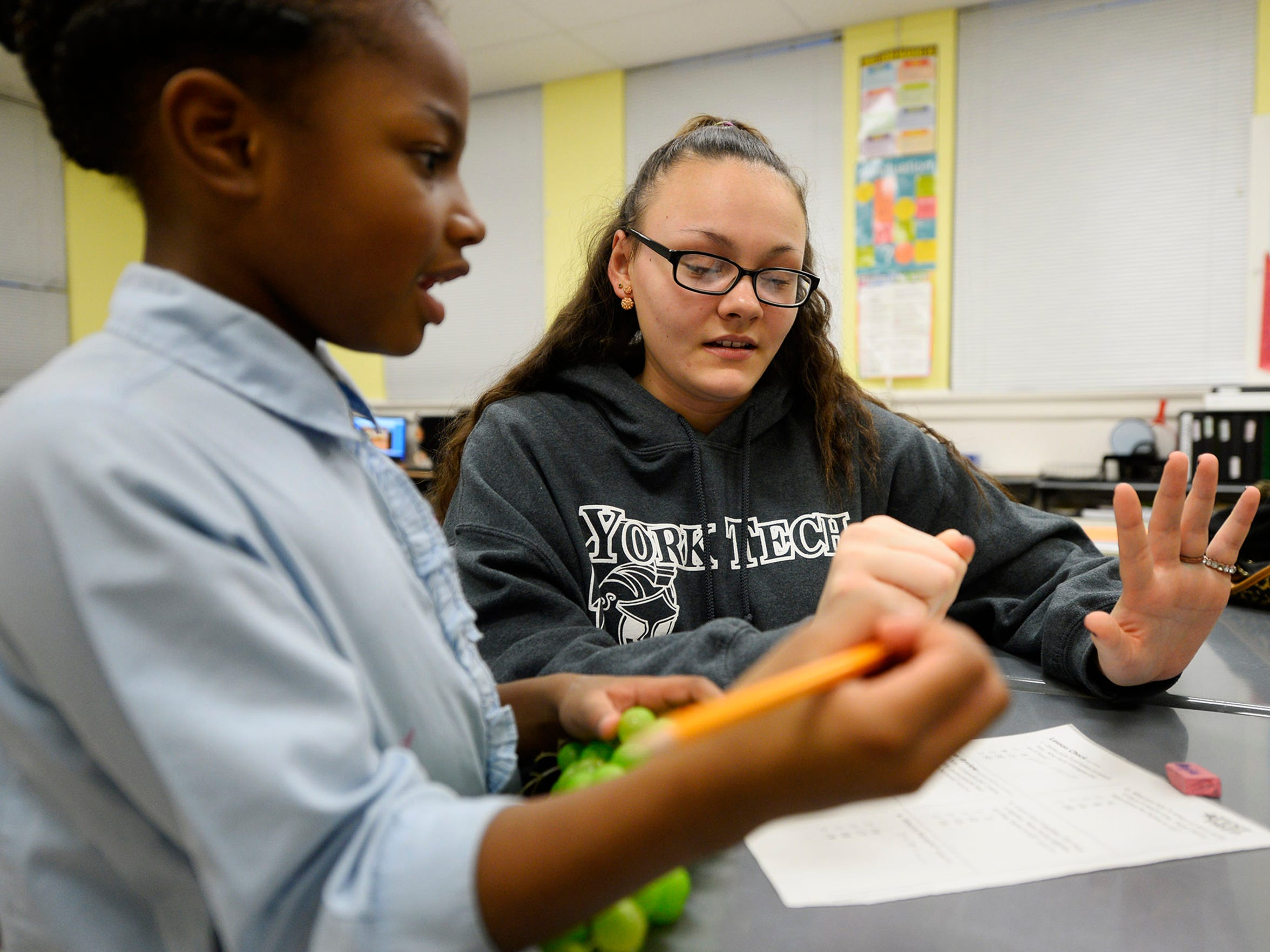 Keiana Rivera, 16, right, helps Aniya Andrews, 7, with her math homework during a YAYA Girls meeting at Helen Thackston Charter School in York earlier this month. Girls spend the first half hour of the meeting doing homework or reading. In the spirit of the sisterhood, the group tries to build, azaleas, ages 12-16, are expected to help the younger girls if they don't have work of their own.