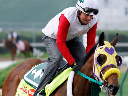Exercise rider Benito Alvarado takes Kentucky Derby hopeful Uncle Sigh for a morning workout at Churchill Downs Tuesday, April 29, 2014, in Louisville, Ky. (AP Photo/Garry Jones)