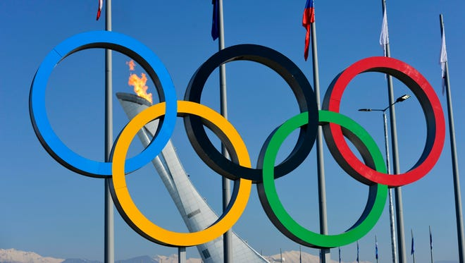 A view of the Olympic cauldron and flame behind the Olympic rings sculpture during the Sochi 2014 Olympic Winter Games.