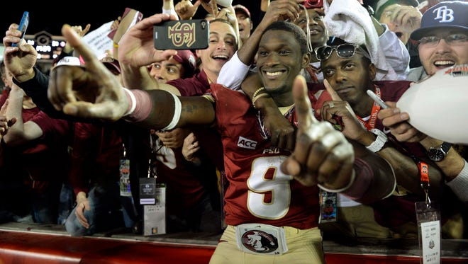 Florida State running back Karlos Williams celebrates with fans in the stands at Rose Bowl Stadium after the Seminoles completed a 14-0 national champion season.