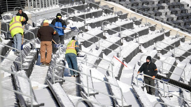 A general view as stadium workers clean snow from the field and stands during the Super Bowl XLVIII stadium preparations press conference at MetLife Stadium.