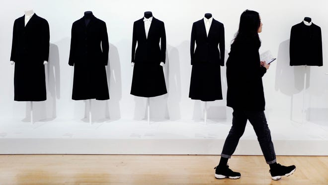 """In this March 16, 2017 photo, a visitor to the Brooklyn Museum in New York walks past a display of black wool suits worn by American artist Georgia O'Keeffe. Exhibit coordinator Lisa Small said O'Keeffe's """"distinctive"""" clothing style symbolized her lifelong commitment to minimalism. O'Keeffe died in 1986 at age 98."""