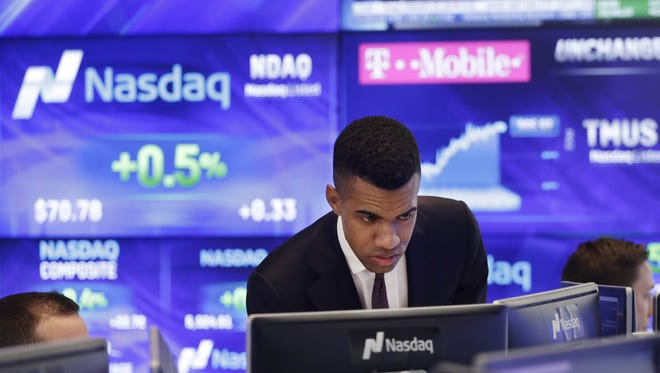 Brad Smith monitors stock prices at the Nasdaq MarketSite, on April 25, 2017, in New York. Information on publicly held companies is available in quarterly reports at this time of year.