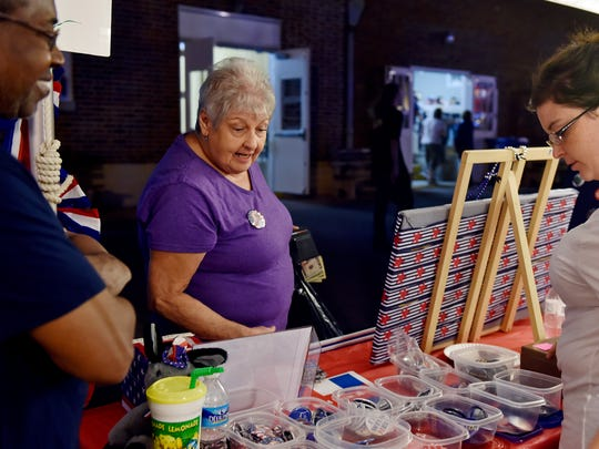 Gloria Klinedinst of York, center, chooses a pin to purchase with help from volunteers George Fleming, left, and Ashleigh Sharland on Sept. 15 at the Democratic Party of York County's booth at the York Fair.