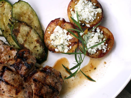 Sunday Supper Apple and honey marinated pork chops with grilled stuffed feta peaches prepared by Test Kitchen Editor Sue Selasky.