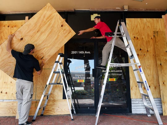 Jared Farias (left) and A.J. Flinchum place the last few plywood boards to the Jetson Builder Appliances storefront in downtown Vero Beach on Wednesday, Sept. 6, 2017, in preparation for Hurricane Irma. The storm is a category 5 hurricane with maximum sustained winds near 185 mph.