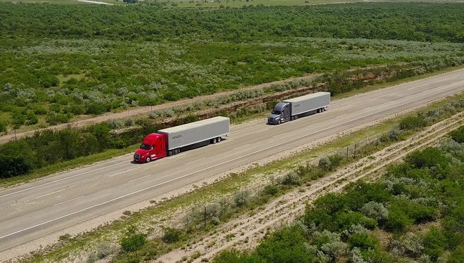 Two trucks 'digitally connected' travel along a highway.