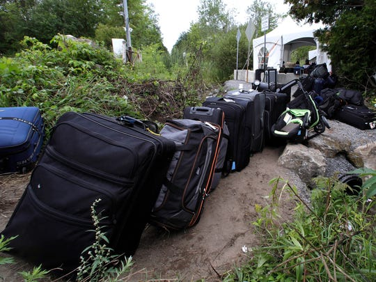 Luggage from migrants fills a pathway at an illegally