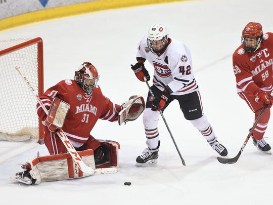 St. ClLoud State's Blake Winiecki tries to get a shot off on MIami goaltender Ryan Larkin during the first period of the Sunday, March 11, game at the Herb Brooks National Hockey Center in St. Cloud.