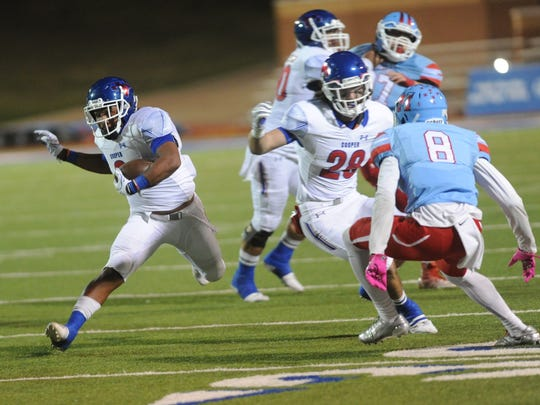 Cooper running back Tyrees Whitfield (3) runs with the ball while fullback Nick Powell (28) tries to block Lubbock Monterey's James Langston (8) during the first of their District 4-5A opener at Lowrey Field in Lubbock. Monterey won the game 51-44 Friday, Oct. 13, 2017.