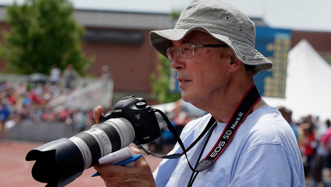 Dave Figi  of wisconsintrackonline.com photographs races during the WIAA state track and field meet in La Crosse.