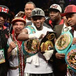 Floyd Mayweather celebrates with his team after improving to 49-0.