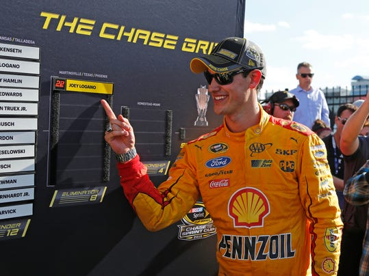 """FILE - In this Oct. 11, 2015, file photo, Joey Logano points to his name on the playoff board after winning the NASCAR Sprint Cup series auto race at Charlotte Motor Speedway in Concord, N.C. Logano scoffed at the seemingly unwritten rule that you don't wreck someone when you're already guaranteed of advancing in the Chase. After all, as he pointed out after spinning Matt Kenseth to win on Sunday, """"The last I checked, NASCAR makes the rules."""" (AP Photo/Terry Renna, File)"""