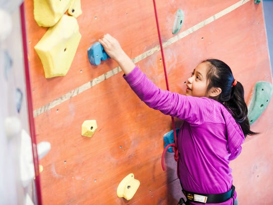 A participant is Streets to Peaks climbs a rock wall