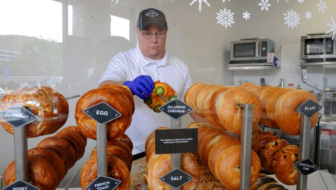 Jay Ellett, owner of  Flatiron Bagel Co. in Thousand Oaks, refills the fresh-out-of-the-oven jalapeño bagels.
