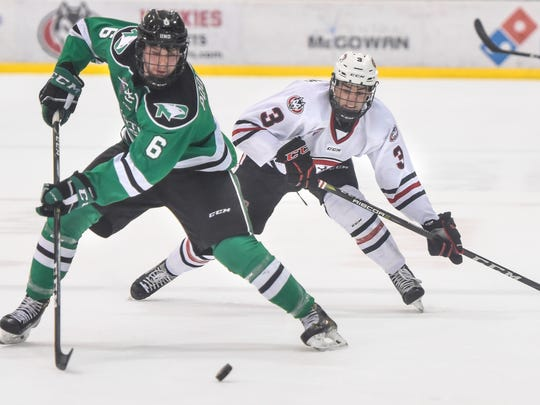 North Dakota's Colton Poolman controls the puck against St. Cloud State's Jack Poehling during the first period of the Saturday, Dec. 9, game at the Herb Brooks National Hockey Center in St. Cloud.