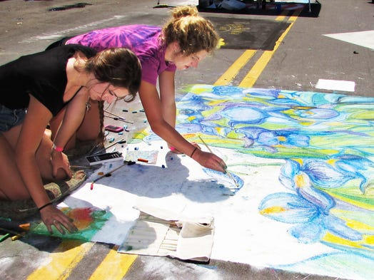 Marissa Faroni, foreground, and Kate Reasons, both of Horseheads, take part in Sunday's Elmira Street Painting Festival.