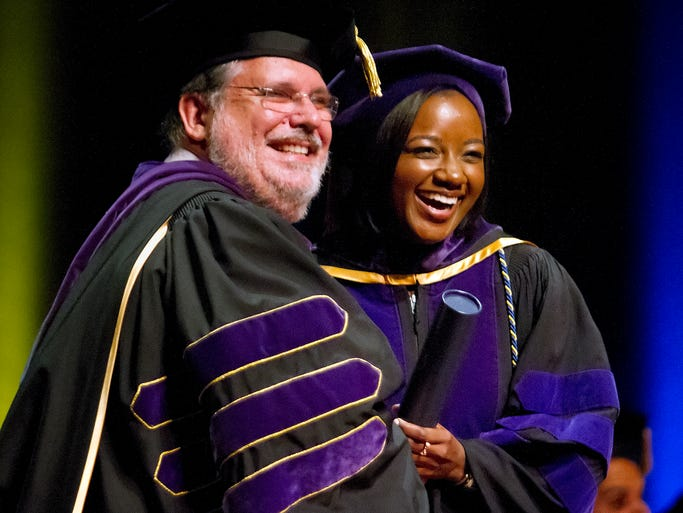 Ave Maria School of Law president Eugene Mihizer, left, awards Charnele Tate her degree during the school's commencement ceremony Saturday at Artis-Naples in Naples.