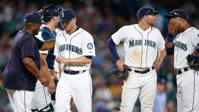 Seattle Mariners pitcher Rob Rasmussen, third from right, walks to the dugout after being relieved for by manager Lloyd McClendon, left, during the eleventh inning of a baseball game Saturday, Aug. 8, 2015, in Seattle. Mariners shortstop Brad Miller, second from right, and second baseman Robinson Cano, right, stand on the mound.
