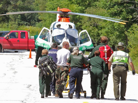 Emergency crews bring former FBI director Louis Freeh, 64, of Wilmington, Del., to a helicopter for transport to Dartmouth Hitchcock Medical Center in Lebanon, N.H., following an Aug. 23 crash on Vermont 12 in Barnard .