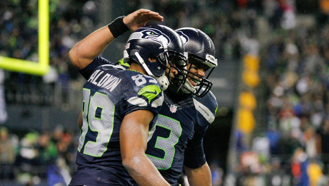 Seattle Seahawks quarterback Russell Wilson (3) celebrates with wide receiver Doug Baldwin (89) after teaming up on a touchdown pass against the New Orleans Saints during the second quarter at CenturyLink Field.