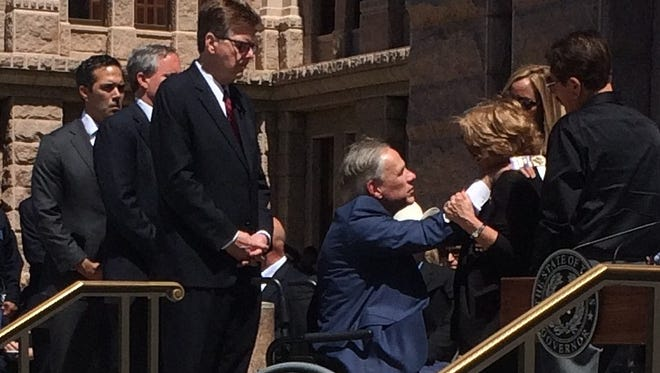 Texas Gov. Greg Abbott comforts the family of El Paso Police Officer David Ortiz at the Texas Capitol on May 1, 2017.