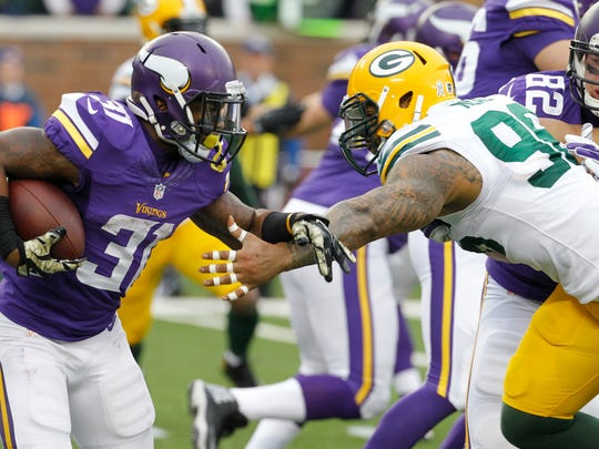 Minnesota Vikings running back Jerick McKinnon, left, runs from Green Bay Packers linebacker Mike Neal, during the first half.