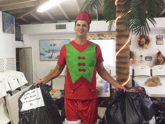 Firefighter serves as one of Santa's elves on the beach.