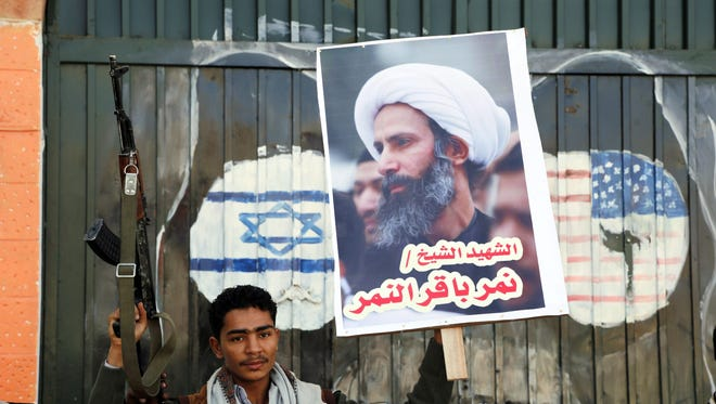 A supporter of Iran-allied Houthi movement holds a gun and a poster of late Shiite cleric Nimr al-Nimr, who was executed in Saudi Arabia, during an anti-Saudi protest outside the Saudi embassy in Sana'a, Yemen, 07 January 2016.